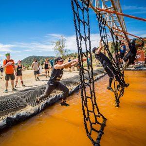 Mulher pulando numa rede de corda acima de um poço de água com lama na Tough Mudder