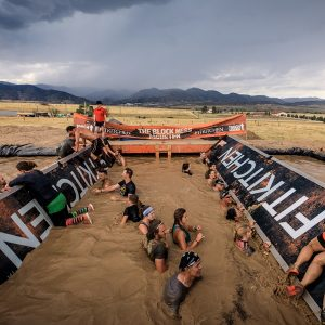 Pessoas dentro de um rio de lama, tentando passar por dois triângulos giratórios nas pontas na Tough Mudder