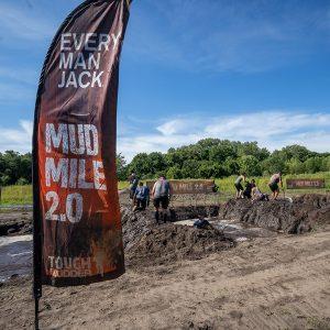 Pessoas tentando atravessar duas trincheiras de lama na Tough Mudder