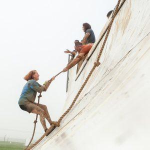 Mulher segurando em corda para tentar escalar rampa na Tough Mudder