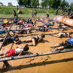 Pessoas rastejando na lama abaixo de uma teia de arames farpados na Tough Mudder