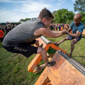 Homens de frente um para o outro com pés no obstáculo e braços entrelaçados fazendo uma espécie de gangorra humana na Tough Mudder